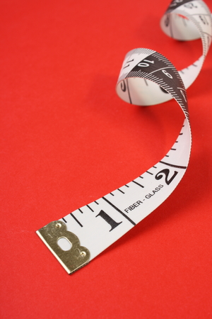 inches: A curled up white tape measure with both inches and centimeters on a red paper