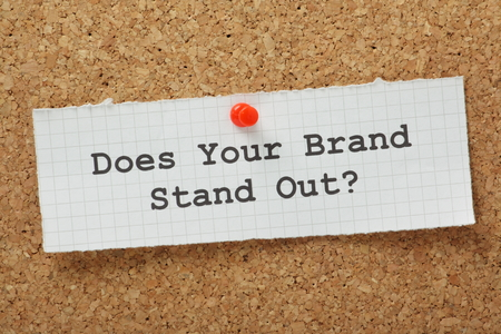 The phrase Does Your Brand Stand Out typed on a piece of graph paper and pinned to a cork notice board  Standard-Bild