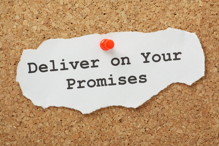 The phrase Deliver on your Promises typed on a scrap of paper and pinned to a cork notice board