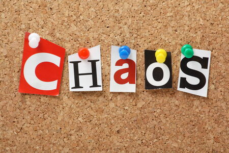 disruption: The word Chaos in cut out magazine letters pinned to a cork notice board