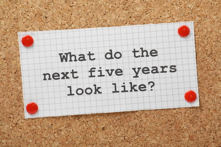 The question What Do The Next Five Years Look Like typed on a piece of graph paper and pinned to a cork notice board  A concept for business planning and looking to the future  Standard-Bild