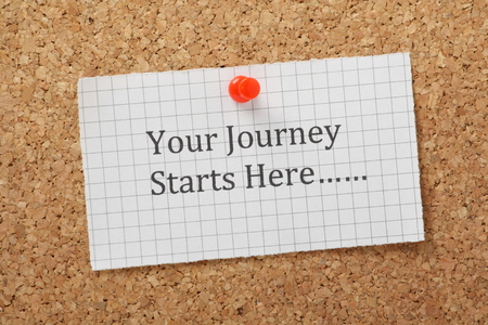 The phrase Your Journey Starts Here typed on a piece of graph paper and pinned to a cork notice board Stock Photo