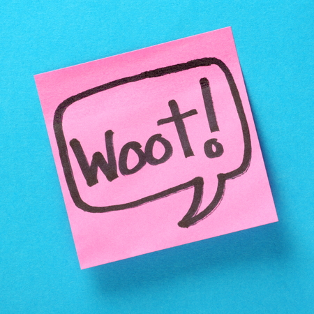 note of exclamation: The word Woot written inside a speech bubble on pink sticky note attached to a blue paper background  Woot is used as an expression of enthusiasm or triumph