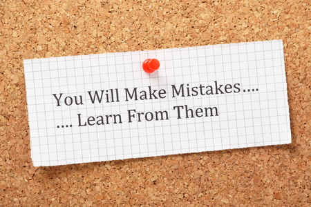 The phrase You Will Make Mistakes, Learn From Them typed on a piece of graph paper and pinned to a cork notice board  A way of empowering people on their road to success
