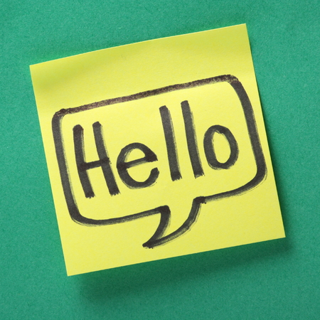 The word Hello written in a speech bubble on a yellow sticky note against a contrasting green paper background photo