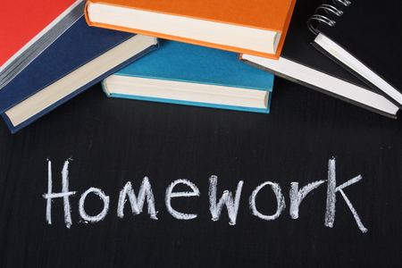 cramming: The word Homework written in chalk on a blackboard next to a pile of school books