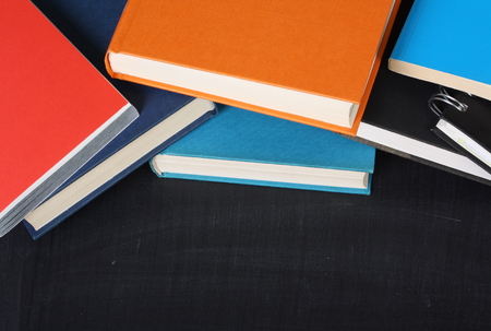 hardback: A pile of school textbooks or hardback books on a blackboard with copy space for your text