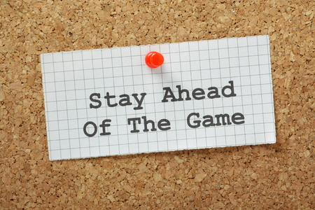 anticipate: Stay Ahead of the Game typed on a piece of graph paper and pinned to a cork notice board  In business this means staying ahead of your competitors and working to anticipate market forces  Stock Photo