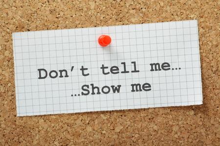 La frase Don t Tell Me, Show Me escribí en un pedazo de papel cuadriculado y cubrió a un tablón de corcho A menudo se utiliza en los negocios, pero más aún como guía para nuevos escritores y reservar