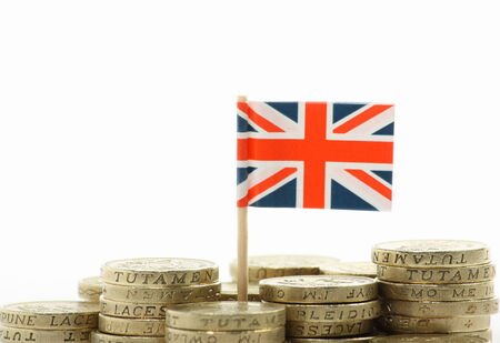 A miniature Union Jack, the flag of Great Britain, stands behind stacks of British Pound Coins on a white background with copy space photo