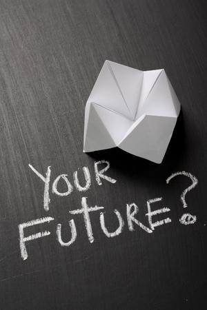 あなたの将来の手によってチョークで書かれた質問の横にある黒板にホワイト ペーパーから作られた折り紙占い師 写真素材
