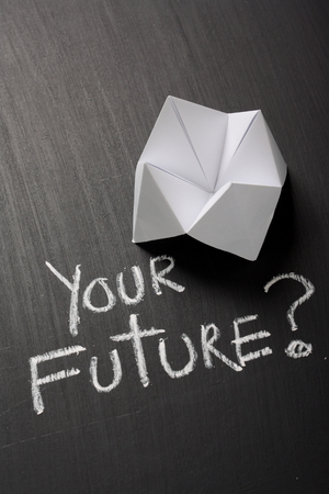 Origami Fortune Teller made from white paper on a blackboard next to the question Your Future  written by hand in chalk