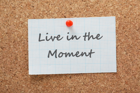 The phrase Live in the Moment printed on a piece of graph paper and pinned to a cork notice board Stock Photo