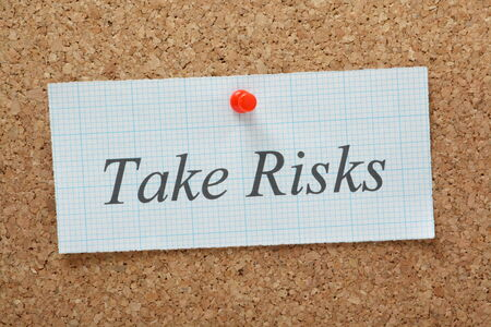 The phrase Take Risks typed on a piece of graph paper and pinned to a cork notice board