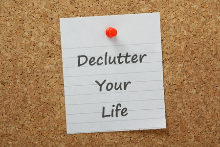 The phrase declutter your life typed on lined paper and pinned to a cork notice board  The process of removing unnecessary distraction drives productivity and efficiency at work and at home