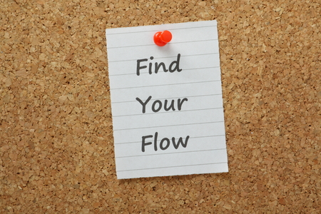 The phrase Find Your Flow typed on lined paper and pinned to a cork notice board  Flow is the state you are in when productivity and creativity are at optimum for efficiency