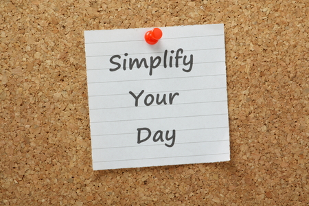 foresight: The phrase Simplify Your Day typed on lined paper and pinned to a cork notice board  If we simplify tasks or projects by breaking them into smaller chunks we are more productive and motivated to work