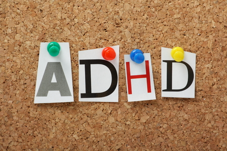 hyperactivity: ADHD the abbreviation for Attention Deficit Hyperactivity Disorder in cut out magazine letters pinned to a cork notice board