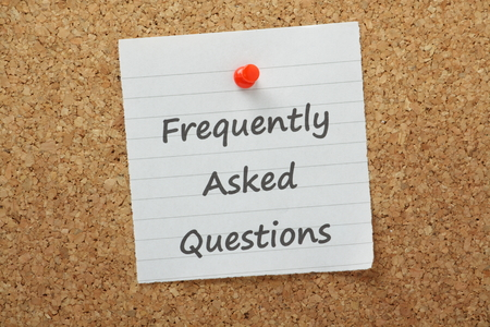 The phrase Frequently Asked Questions typed on piece of lined paper and pinned to a cork notice board