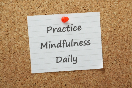 La frase practicar la atención diaria en un pedazo de papel clavado en un tablón de anuncios de corcho Un estado mental obtendrán centrando la conciencia en el presente a través de la meditación