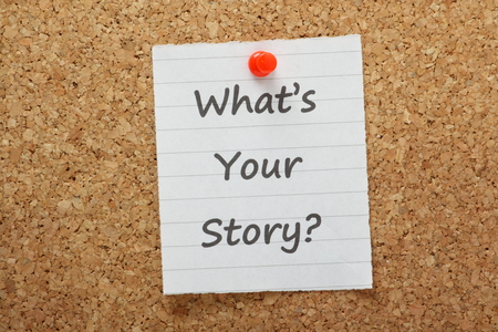 The phrase What s Your Story typed on a piece of lined paper pinned to a cork notice board