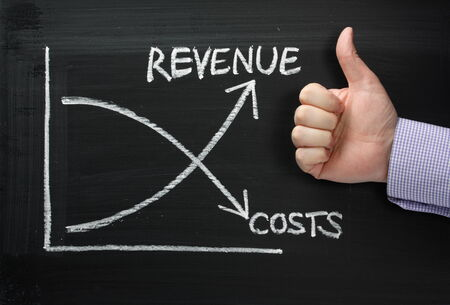 Revenue Versus Costs graph on a Blackboard with a hand giving the Thumbs Up sign Stock Photo
