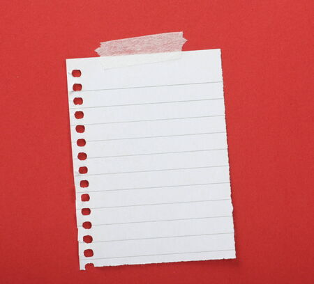 taped: Piece of lined paper taped to a red background with copy space