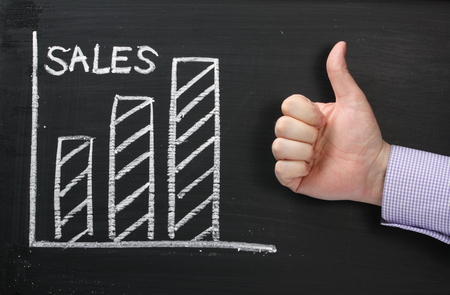 A graph showing Sales rising on a blackboard with a hand in a business shirt giving the okay thumbs up photo