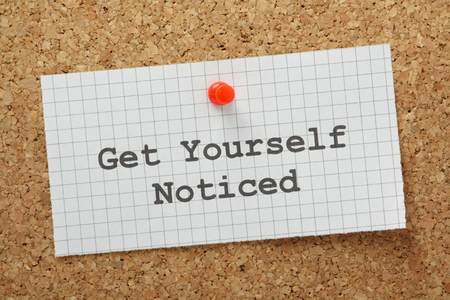 The phrase Get Yourself Noticed typed on a piece of graph paper and pinned to a cork notice board Standard-Bild