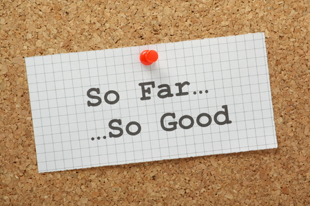 so: The phrase So Far, So Good typed on a piece of graph paper and pinned to a cork notice board Stock Photo