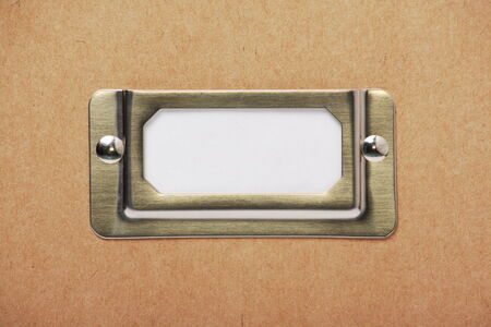 A blank label in a metal holder on the outside of a cardboard box Stock Photo