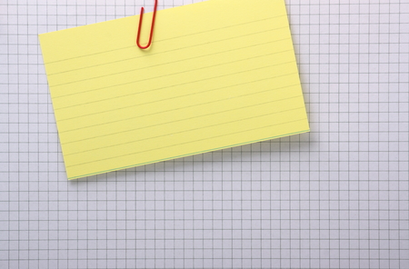 A yellow index card clipped with a paperclip to a grey lined sheet of graph paper with copy space photo