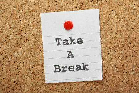 The phrase Take A break typed on a paper note and pinned to a cork notice board photo