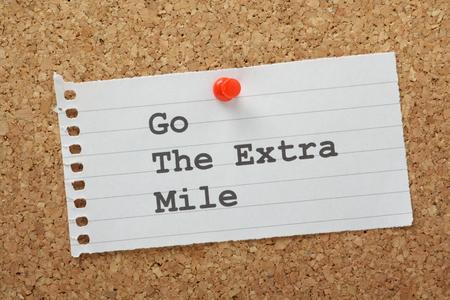 exceeding: La frase Ir La Milla Extra escribe en un pedazo de papel de nota alineado y clavado en un tabl�n de corcho Foto de archivo