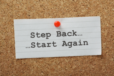 The phrase Step Back and Start Again typed on a paper note and pinned to a cork notice board  Sometimes in business and in life we have to take a step back and change direction  photo