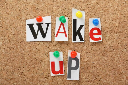 The phrase Wake Up in cut out magazine letters pinned to a cork notice board photo