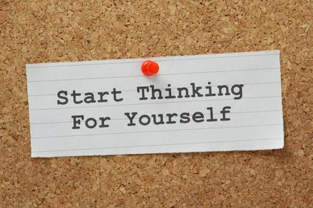 autonomia: La frase empezar a pensar por usted mismo escribe en un pedazo de papel y clavado en un tabl�n de corcho Foto de archivo