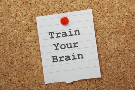 De zinsnede Train Your Brain getypt op een stuk papier en vastgemaakt aan een kurk prikbord