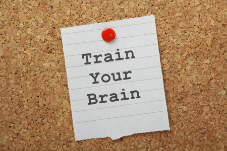 The phrase Train Your Brain typed on a piece of paper and pinned to a cork notice board