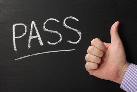 pass test: The word Pass written on a blackboard with a male hand giving the thumbs up sign for success