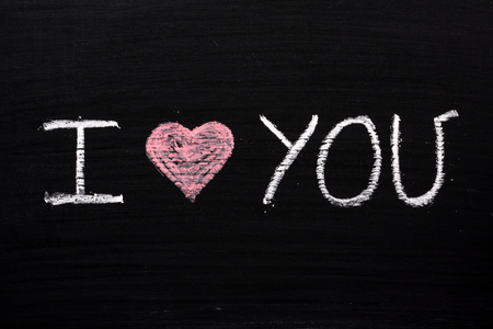 love confession: The phrase I love You with a red heart symbol written by hand in chalk on a blackboard Stock Photo
