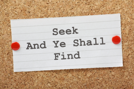 ye: The phrase Seek and Ye Shall Find typed on a piece of paper and pinned to a cork notice board  Stock Photo