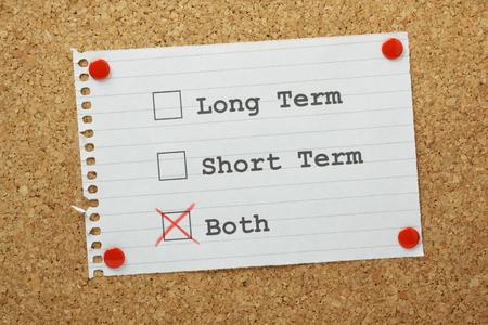 長いコルク板に固定されている長期的、短期的またはアラームの両方のチェック ボックスまたは短期的には私たちの人生の目標やビジネス プランに 写真素材