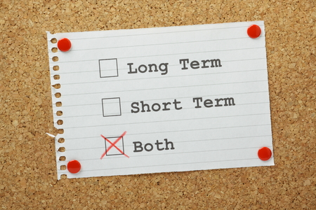 Tick boxes for long term, short term or both on a reminder pinned to a cork notice board  Long or short term can be applied to our life goals or business plans and it is best to have both Stock Photo - 28109815