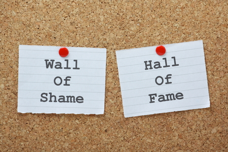 Wall of Shame or Hall of Fame choices on a cork notice board Stock Photo