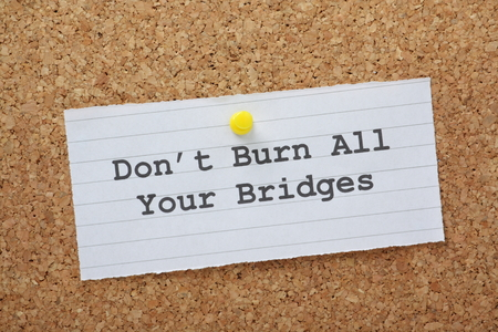 The phrase Don t Burn All Your Bridges on a paper note pinned to a cork notice board as a reminder