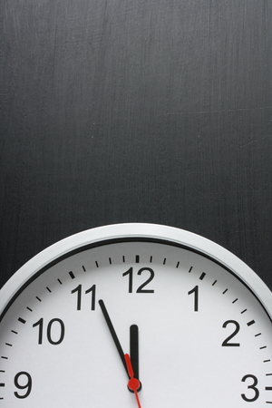 Clock with the time approaching midnight and copy space on a used blackboard photo