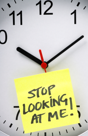 Yellow sticky note with the message Stop Looking At Me written on it and stuck to an office wall clock, as a concept for clock watching at work or school  photo