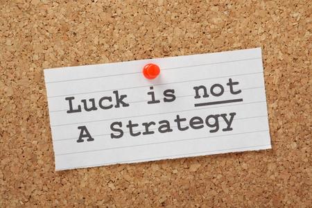 planeaci�n estrategica: La suerte frase no es una estrategia en un tabl�n de corcho como un recordatorio de que sus planes de negocio o de vida no pueden tener �xito en la buena fortuna por s� solo Foto de archivo