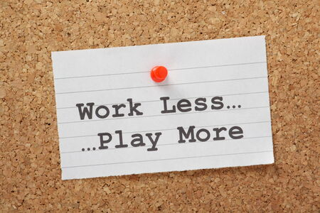 The phrase Work Less Play More typed on a paper note and pinned to a cork notice board as a reminder photo